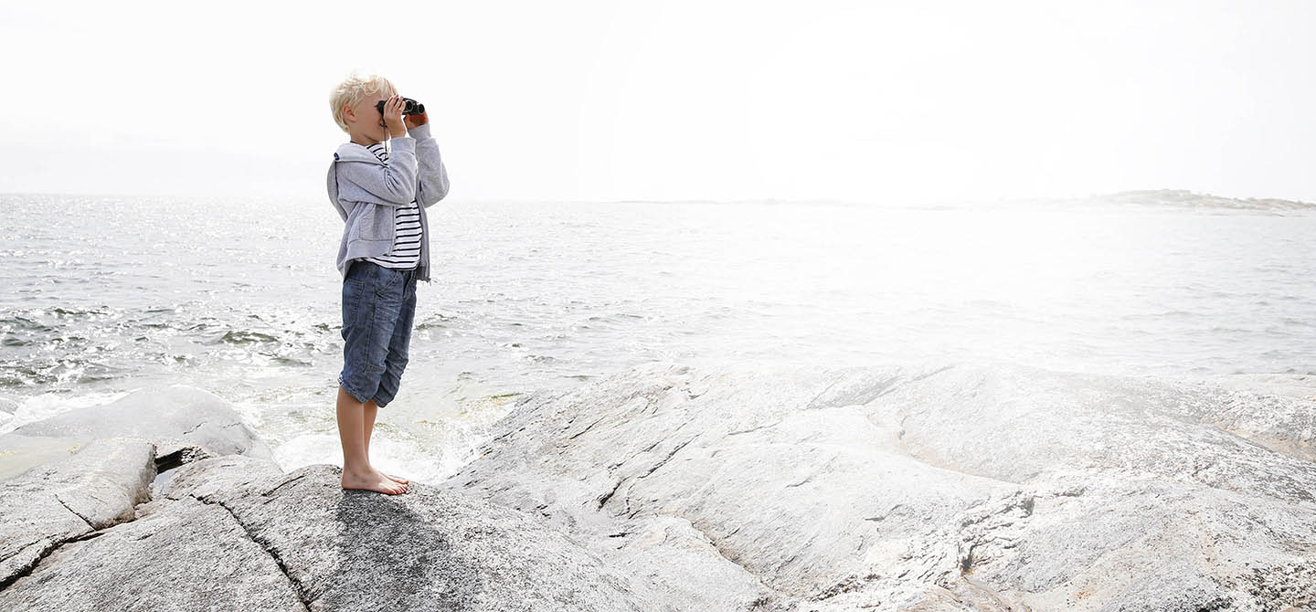Poika seisoo kalliolla meren rannalla ja katsoo kiikareilla. A boy standing on a rock looking at the ocean with binoculars
